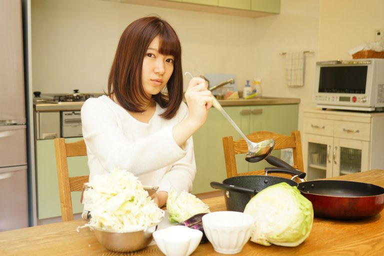 Young woman using a smartphone while cooking
